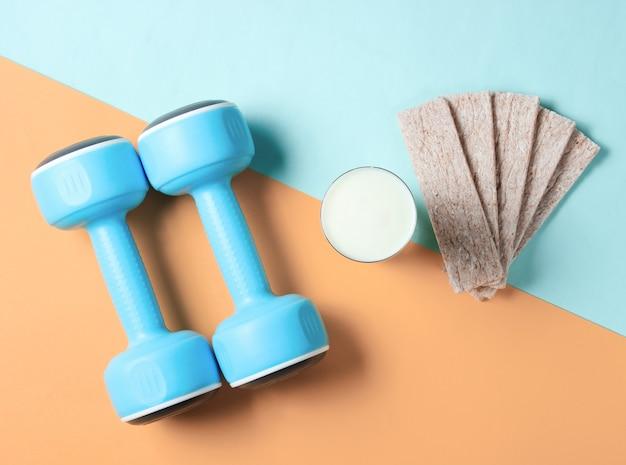 Ajuste o conceito de emagrecimento. halteres, copo de kefir, pão crocante diet em uma laranja azul