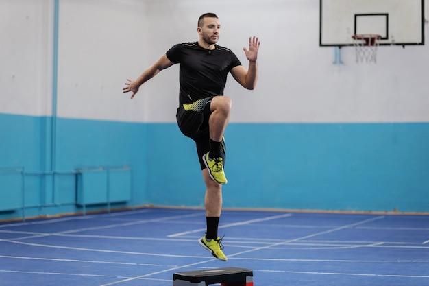 Ajuste o esportista dedicado em forma dando passos de estocada no pavilhão desportivo.