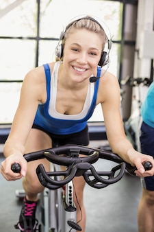Ajuste o grupo de pessoas que usam bicicleta ergométrica juntos em crossfit