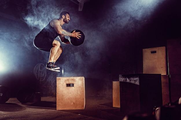 Ajuste o homem barbudo tatuado pulando em uma caixa como parte da rotina de exercícios. homem fazendo salto de caixa no ginásio. atleta está realizando saltos de caixa