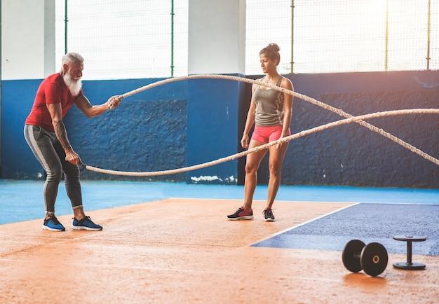 Ajuste o homem com corda de batalha no ginásio de fitness de treinamento funcional - personal trainer motivando o atleta do sexo masculino dentro do centro de bem-estar clube - conceito de tendências de treino e esporte - foco no corpo do homem