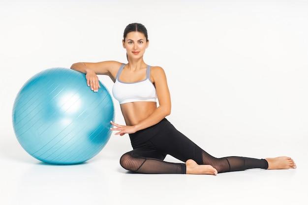Ajuste o instrutor de pilates jovem morena mostrando exercícios diferentes com equipamentos básicos de pilates, incluindo uma bola. fundo branco