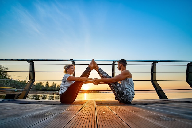 Ajuste o jovem casal fazendo acro ioga no cais à beira-mar estilo de vida saudável pessoas atividade esportiva ao ar livre ...