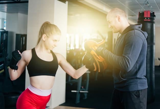 Ajuste o soco de treinamento de mulher loira com treinador de homem. na academia. casal fazendo exercícios de soco