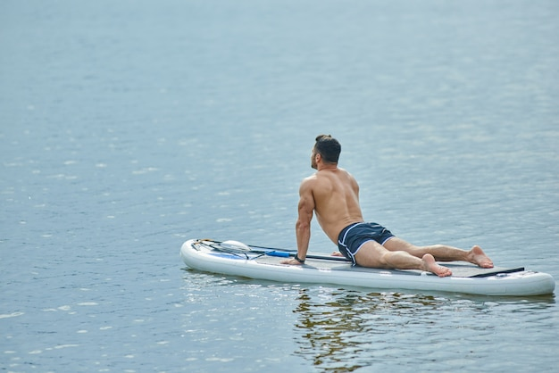 Ajuste perfeito homem fazendo exercícios de alongamento, deitado a bordo do sup, nadando no lago da cidade.
