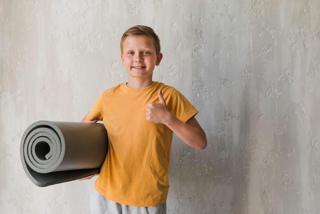 Ajuste sorridente menino segurando enrolado colchonete mostrando os polegares para cima o sinal na frente do pano de fundo concreto