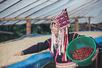 Akha mulheres sorriu e levou uma cesta de café