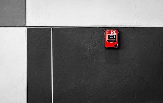 Alarme de incêndio no muro de concreto preto e branco