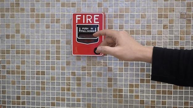 Alarme de incêndio ou alerta ou equipamento de aviso de campainha e mão direita. no edifício para emergência e segurança.