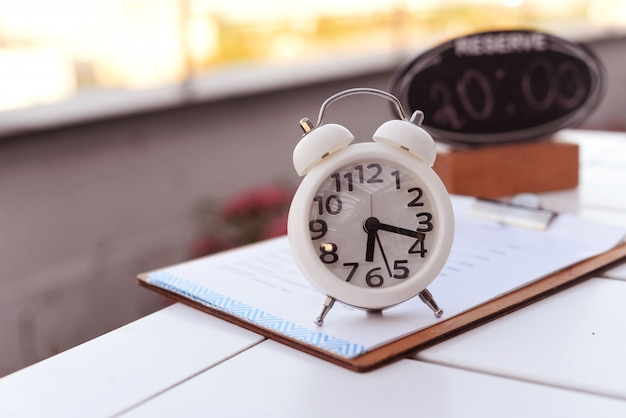 Alarme de relógio branco com uma plataforma giratória na mesa do lado de fora em um restaurante