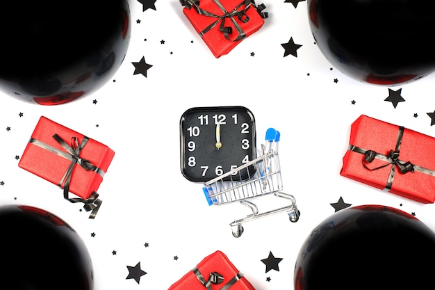 Alarme e mini carrinho de compras com balões pretos e caixas de presente. composição de compras e vendas. venda de sexta-feira negra. segunda-feira cibernética.