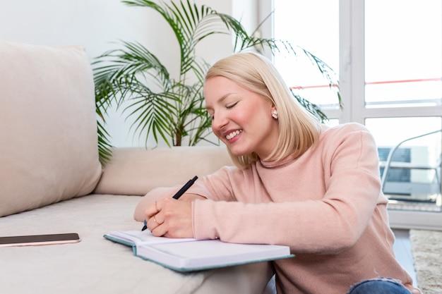 Albino feliz mulher sentada no chão acarpetado enquanto estudava suas lições usando um livro com notas.