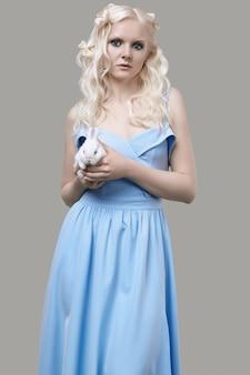 Albino menina loira elegante vestido posando com coelhinho fofo