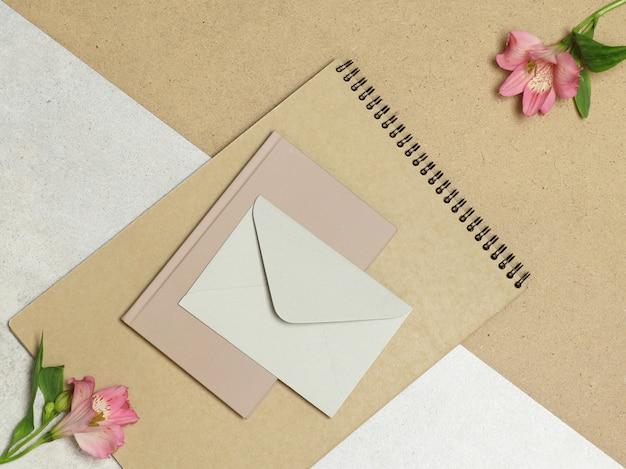 Álbum de artesanato, notas, envelope com flores rosa na mesa de madeira e pedra