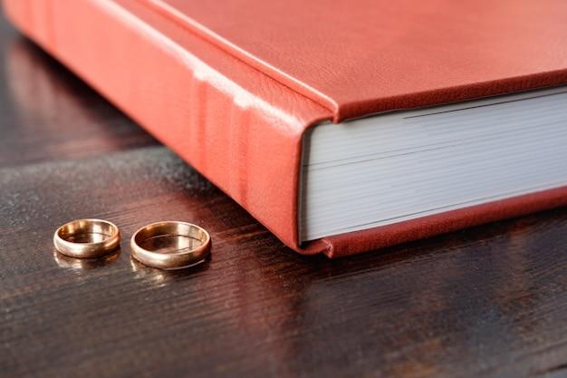 Álbum de casamento marrom com dois anéis de casamento deite na mesa de madeira marrom