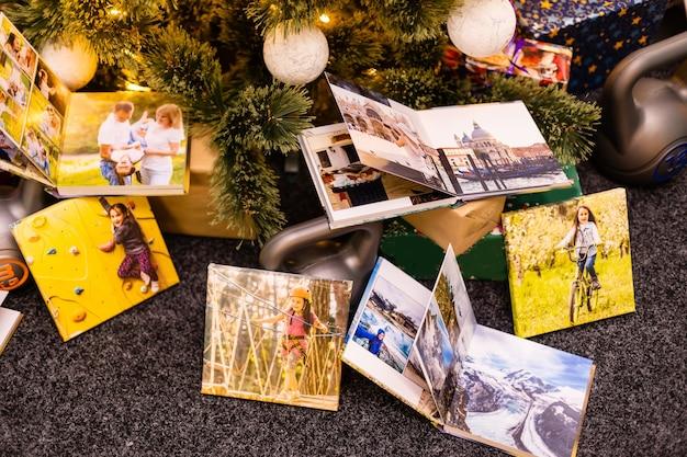 Álbum de fotos, álbum e pesos para esportes perto da árvore de natal como um feriado de presente