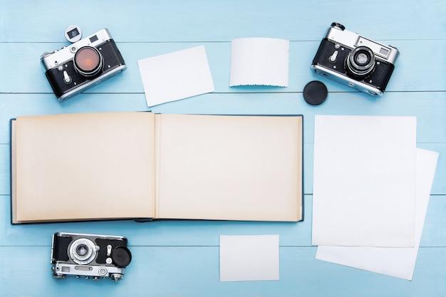 Álbum de fotos antigo com fotos em uma linda mesa de madeira e câmeras antigas.