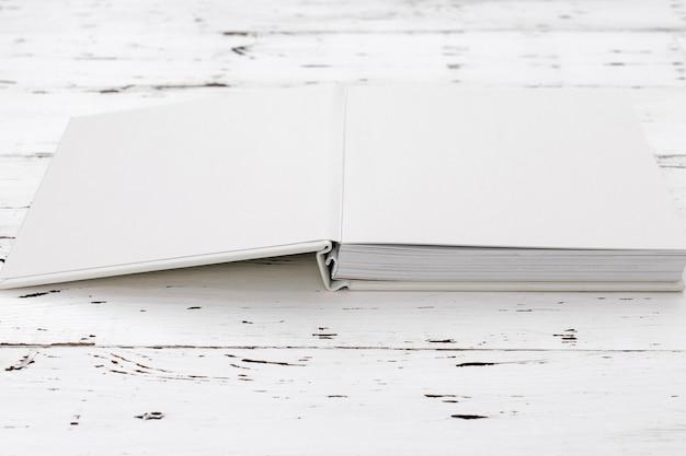 Álbum de fotos de casamento branco na mesa de madeira
