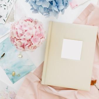 Álbum de fotos de casamento de família, buquê de flores de hortênsia colorida em tons pastéis, cobertor cor de pêssego, pincel de aquarela, decoração na superfície branca
