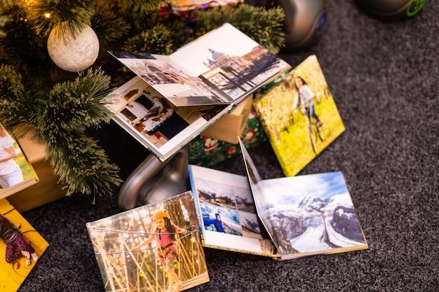 Álbum de fotos de família e pesos para esportes perto da árvore de natal
