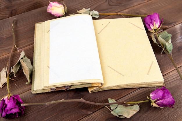 Álbum de fotos vintage na madeira com flores secas.