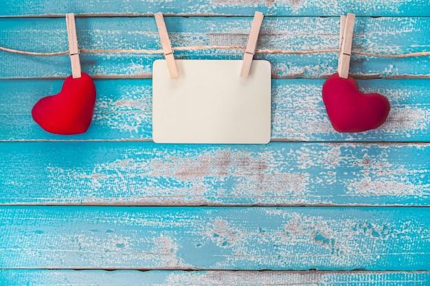 Álbum de quadro de fotos em branco e coração vermelho pendurado no fundo de madeira azul vintage