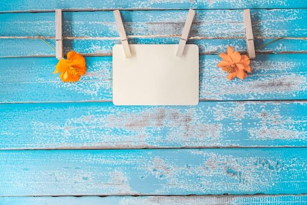 Álbum de quadro de fotos em branco e flores penduradas no fundo de madeira azul vintage