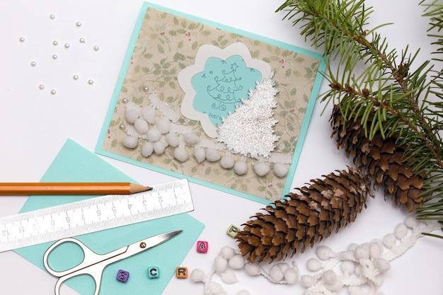 Álbum de recortes, cartão de natal e ferramentas com decoração
