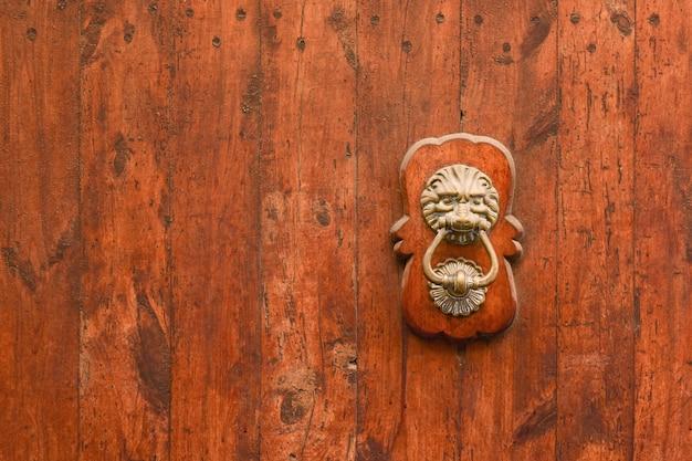 Alça de latão em forma de cabeça de leão com um anel em seus dentes no antigo portão de madeira