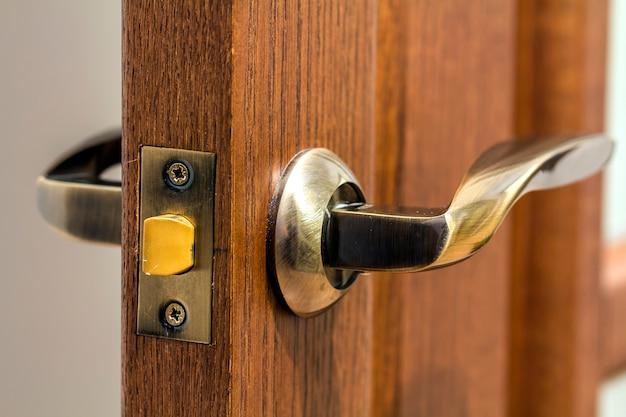 Alça moderna e contemporânea de metal acetinado em um close-up da porta de madeira.