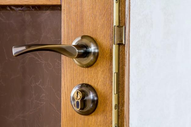 Alça moderna e contemporânea em metal acetinado e uma fechadura com chave em um close de porta de madeira.
