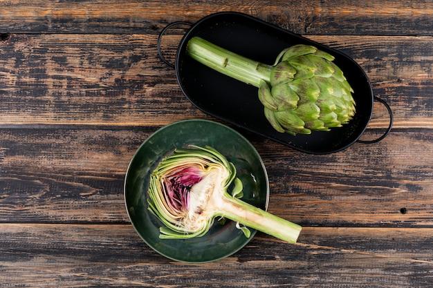 Alcachofra e fatia em uma panela e prato com vista superior em um escuro de madeira