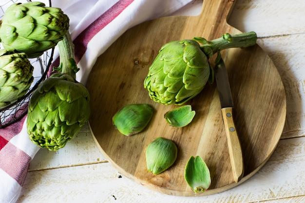 Alcachofra fresca descascada, preparando-se para cozinhar, placa de corte de madeira, faca, legumes na cesta