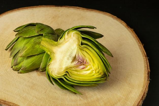 Alcachofra fresca é cortada ao meio em uma placa de madeira.