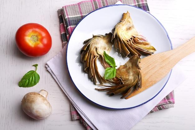 Alcachofras assadas no prato, na superfície da mesa da cozinha