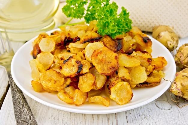 Alcachofras de jerusalém fritas em um prato, tubérculos frescos, guardanapo, salsa, óleo vegetal em um fundo de prancha de madeira branca
