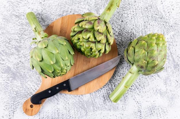 Alcachofras em uma tábua com vista superior da faca em um cinza claro