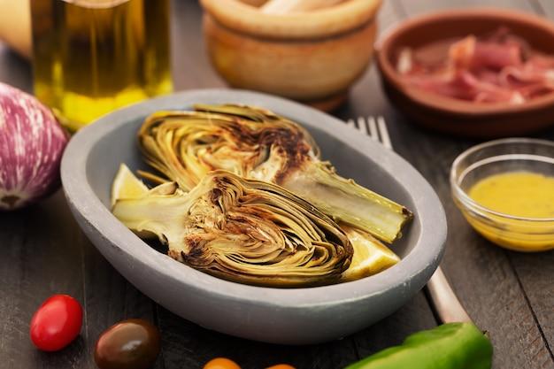 Alcachofras grelhadas e legumes em cima da mesa