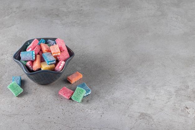 Alcaçuz colorido em uma tigela preta redonda colocada sobre uma superfície de mármore