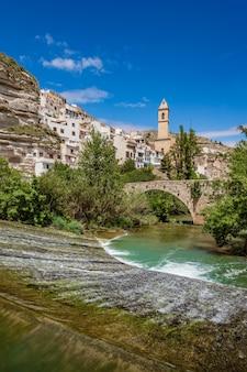 Alcala del jucar idílica cidade espanhola branca com uma ponte de pedra sobre um rio e um campanário