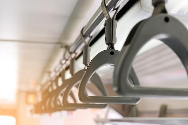 Alças de plástico cinza nos trilhos do teto para passageiros em pé no sistema ferroviário subterrâneo mrt