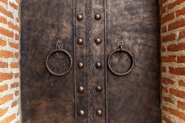 Alças redondas de ferro em um antigo portão de metal. maçaneta da porta de ferro antigo.