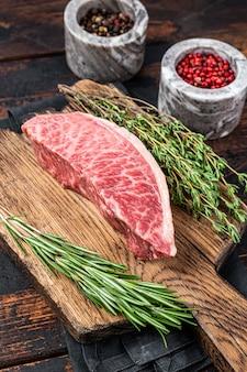 Alcatra crua wagyu a5 ou bife do lombo, carne de boi kobe em um tabuleiro de açougue. fundo de madeira escuro. vista do topo.