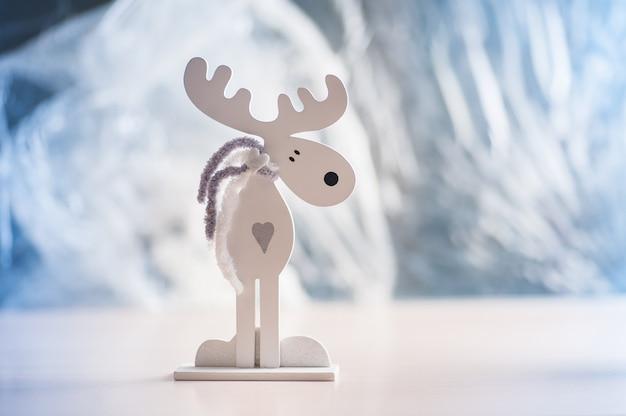 Alce de madeira branco em uma luz. decorações de natal