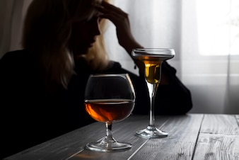 Álcool bebendo da mulher sozinho olhando para fora sua janela.