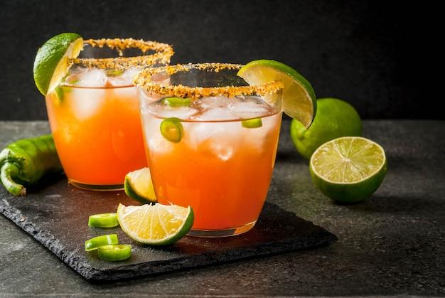 Álcool. cocktail mexicano sul-americano tradicional. michelada picante com pimentas de jalapeno quentes e limão. em uma mesa de pedra escura. copyspace