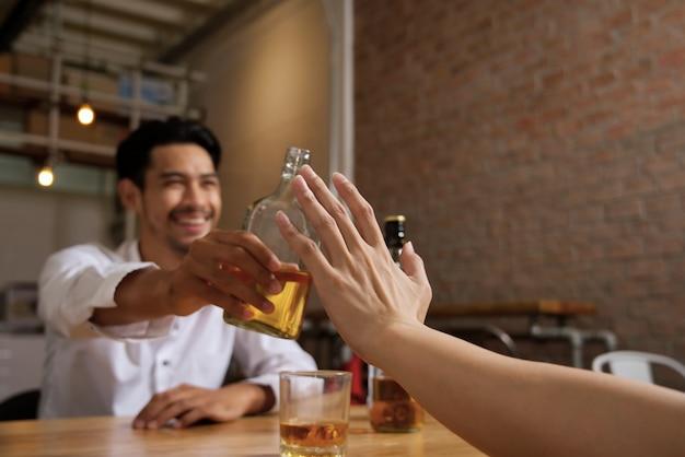 Álcool da recusa da mão do homem que senta-se oposto ao lado da tabela que guarda a garrafa do uísque.