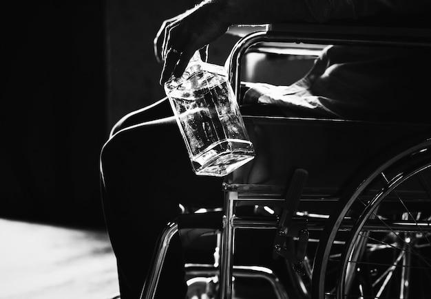 Alcoólatra homem sentado em uma cadeira de rodas