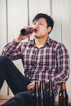 Alcoólico homem asiático sentado sozinho bebendo cerveja