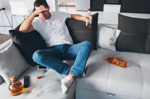 Alcoólicos sentam no sofá entre garrafas abertas com uísque. sofra de ressaca ou dor de cabeça. sozinho com problemas. desesperado e sem esperança.